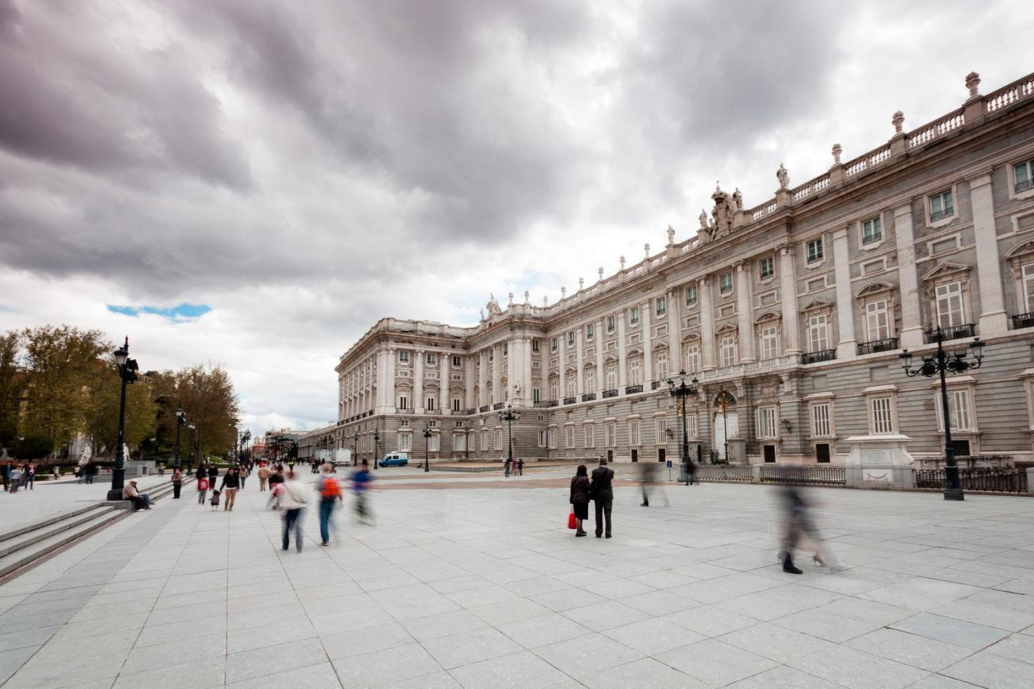 Tourists Walk Outside The Royal Palace Of Madrid