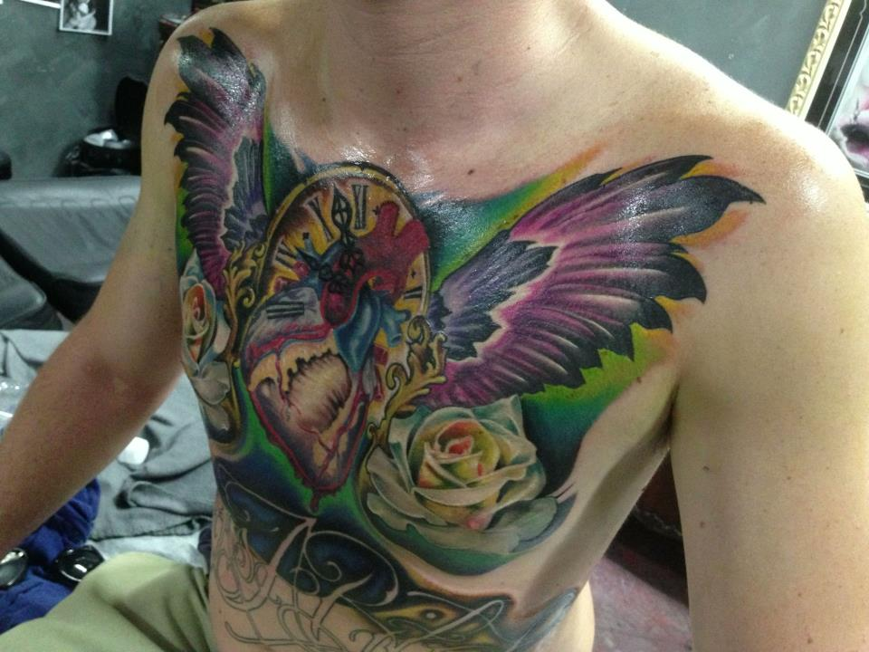 Traditional Real Heart With Wings And Clock Tattoo On Man Chest