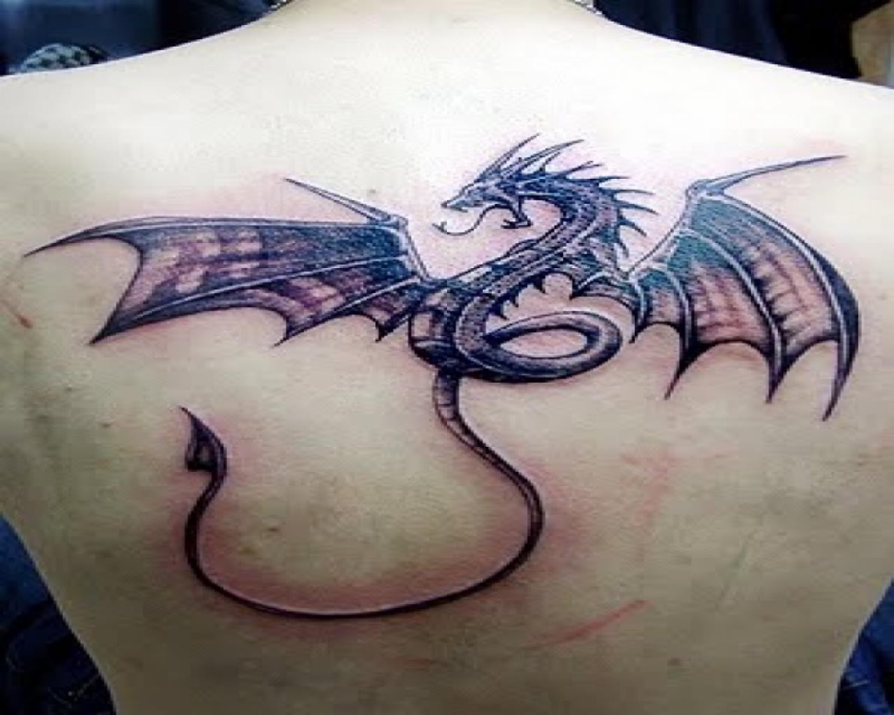 Impressive black tribal dragon tattoo on man upper back for Black tribal tattoo ink