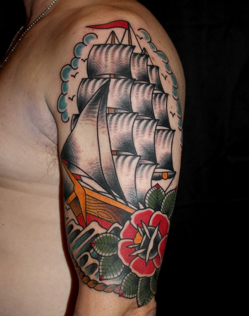 Traditional Ship With Flower Tattoo On Left Half Sleeve