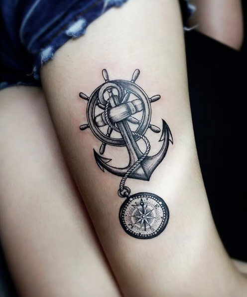 Black Ink Anchor With Ship Wheel And Compass Tattoo On Left Thigh