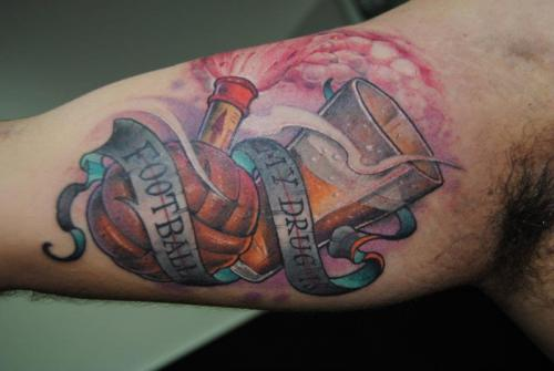 Football With Banner Tattoo On Right Bicep