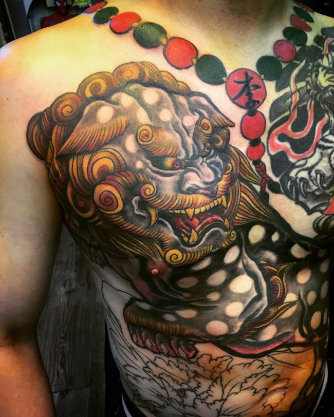 traditional foo dog tattoo on man chest. Black Bedroom Furniture Sets. Home Design Ideas