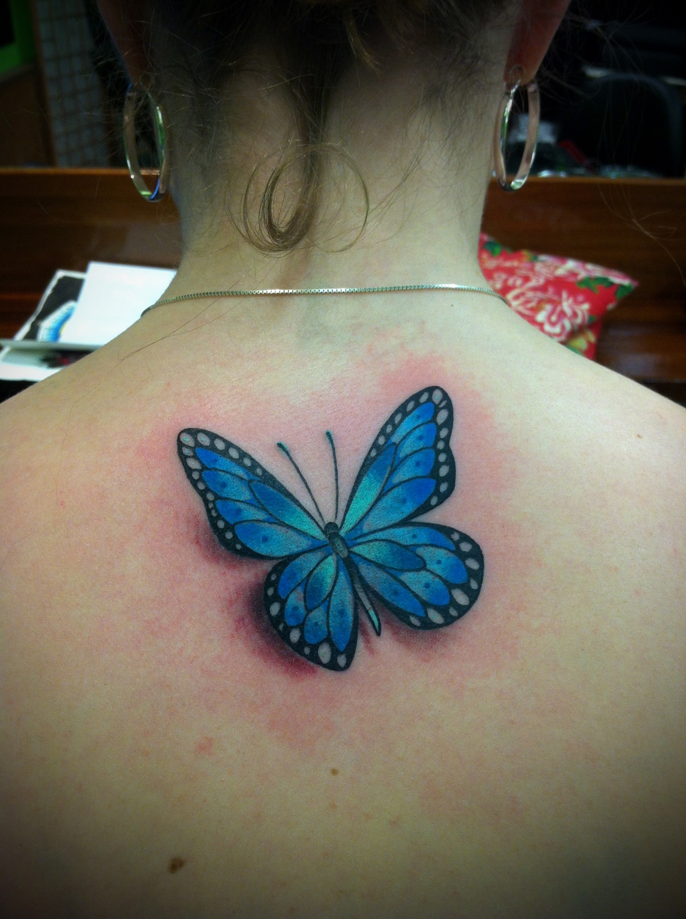 Blue Ink Butterfly Tattoo On Girl Upper Back