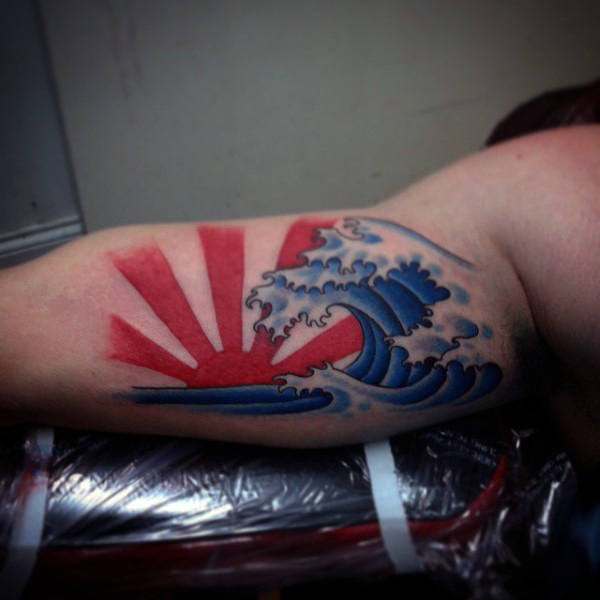 Blue Ink Water Waves And Rising Sun Tattoo On Inner Bicep