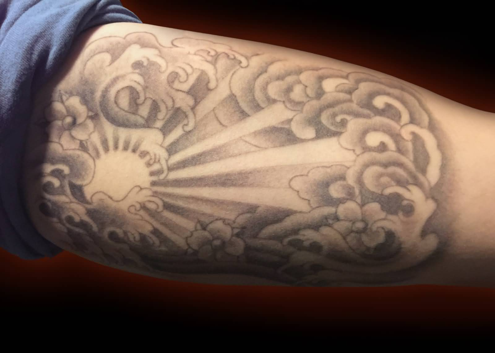 Grey Ink Clouds And Sun Tattoo On Bicep