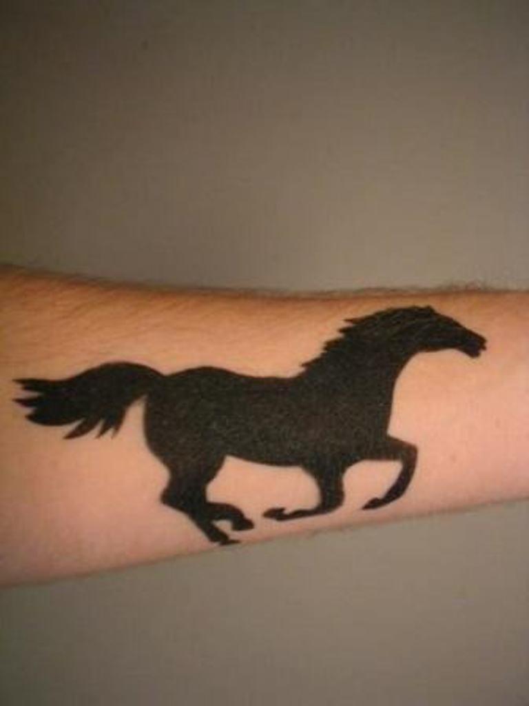 Black silhouette running horse tattoo on forearm for Running horse tattoo