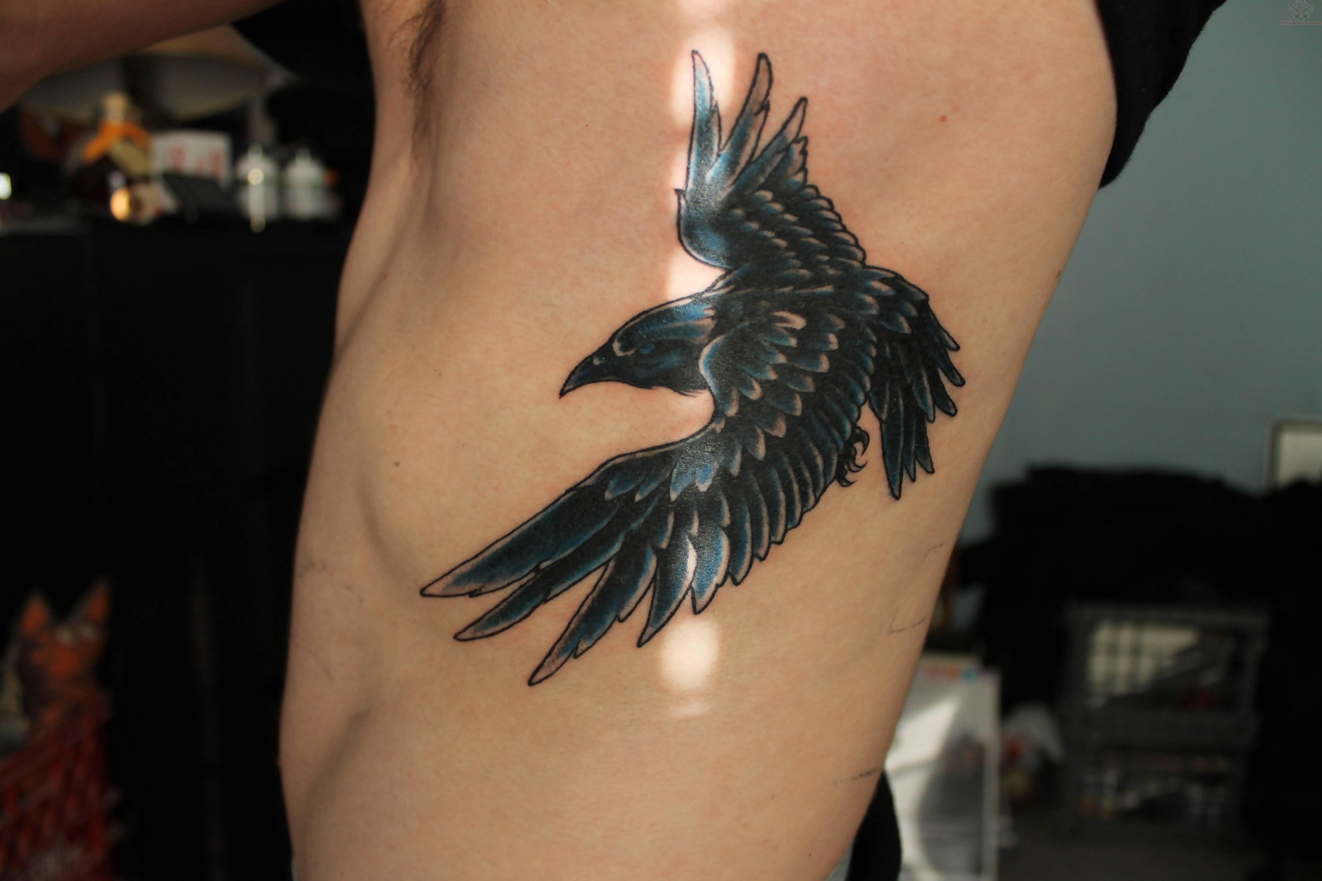 63 latest raven tattoos ideas blue and black flying raven tattoo on man side rib buycottarizona Gallery