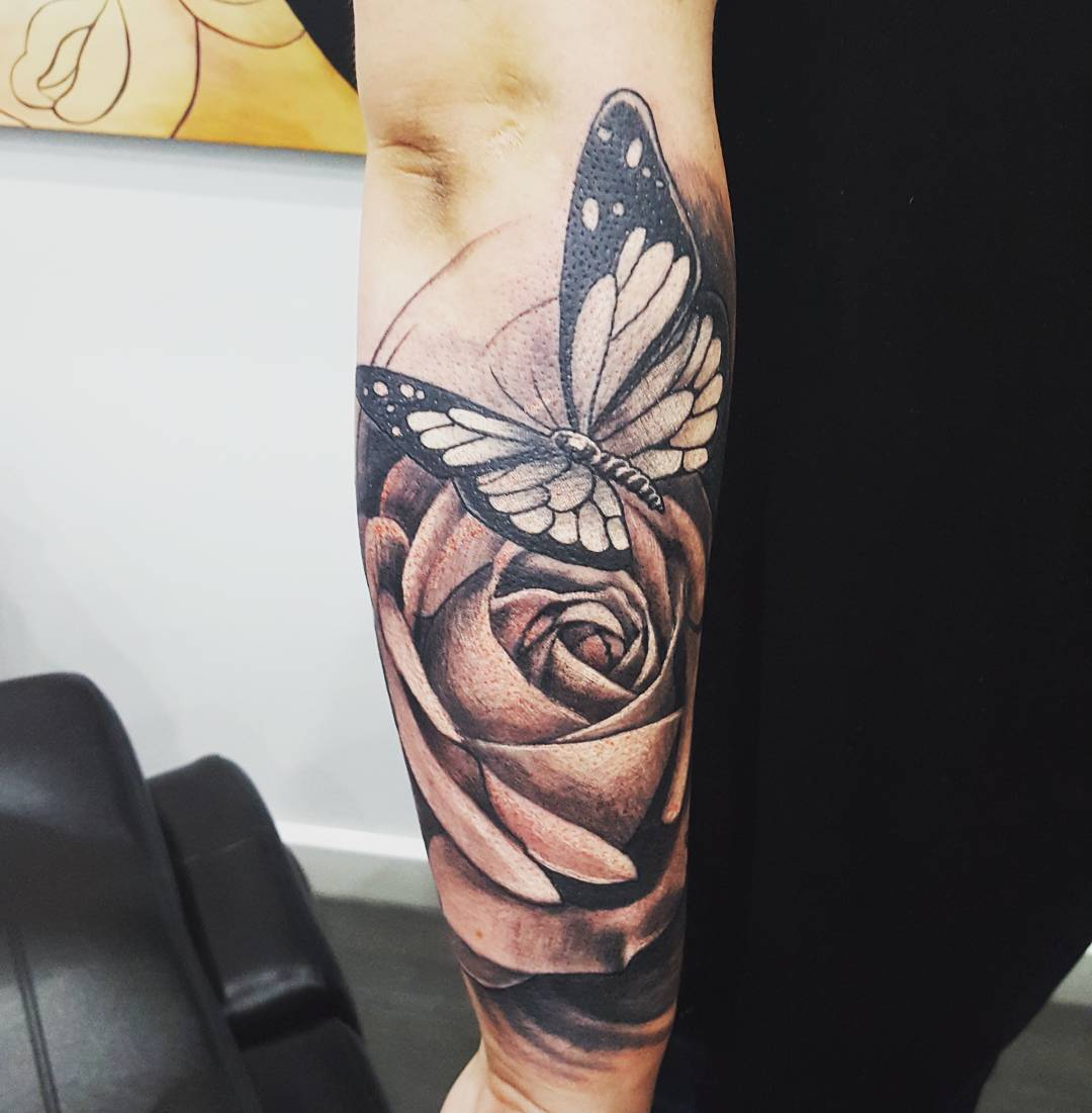 Black grey ink large rose butterfly tattoo on arm for Butterfly tattoo arm designs