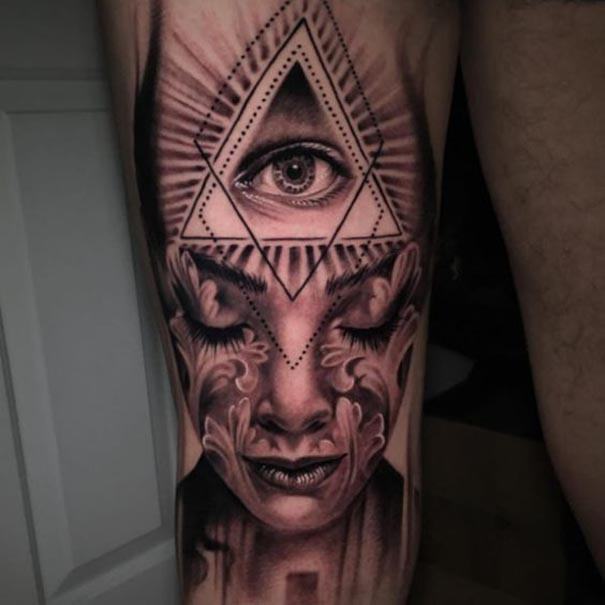 Unique Grey Ink Girl Face And Glowing Illuminati Tattoo On Leg