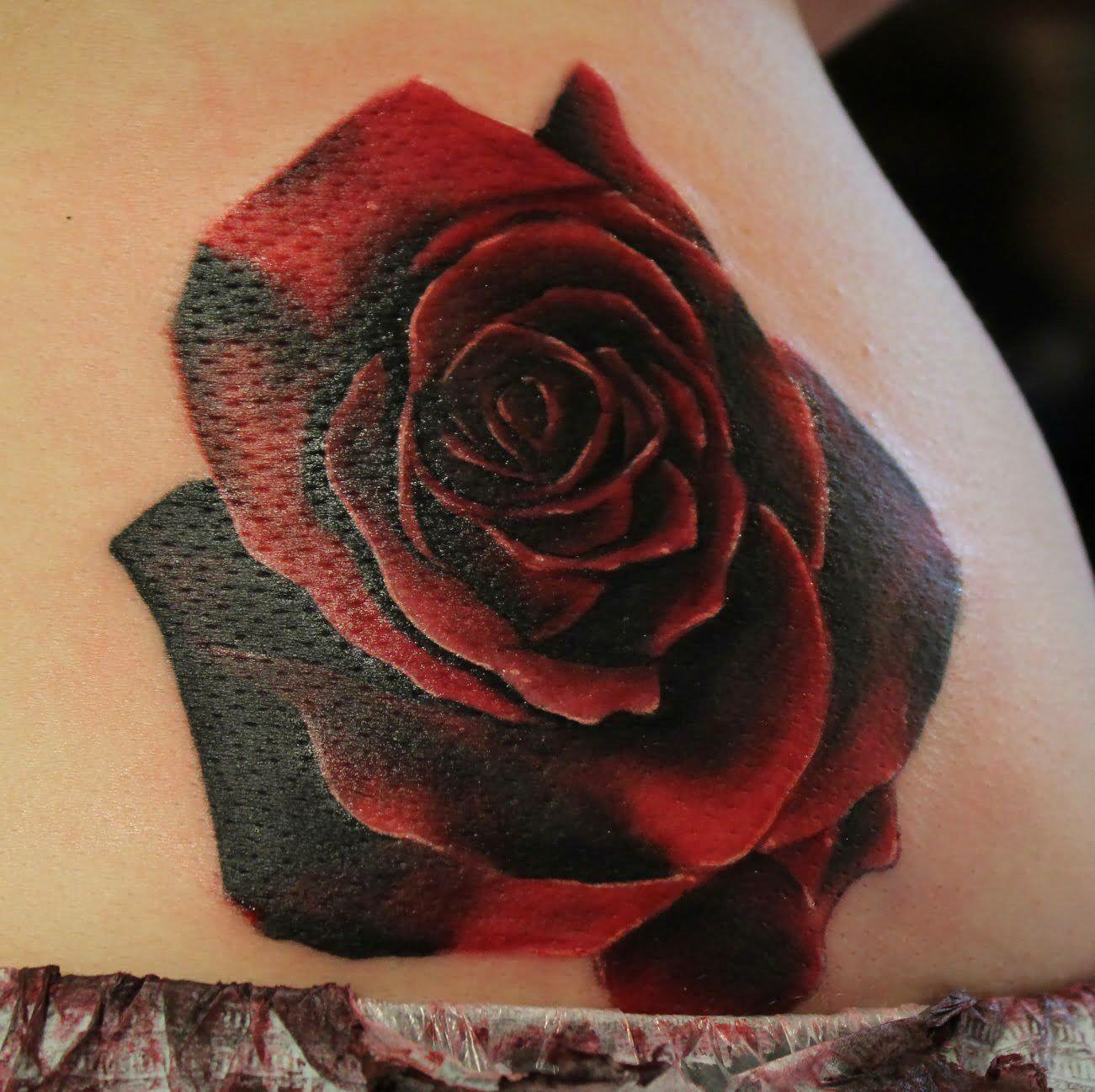 Dark black and red rose tattoo on shoulder for Red rose tattoo meaning