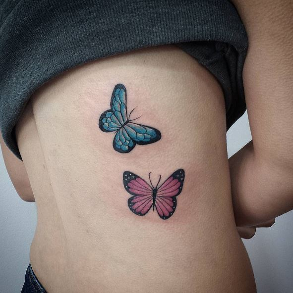 ad29ae778 Red and blue butterfly pair tattoo on right middle back