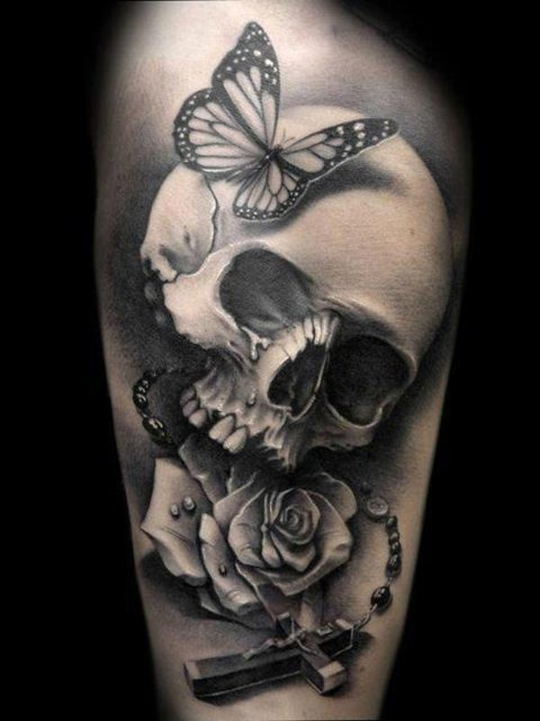 Black And Grey Skull Butterfly Celtic Cross And Rose Tattoo On Arm