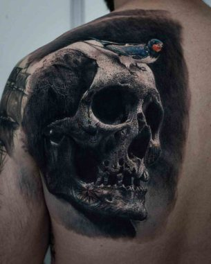 Black Shaded Skull And Bird Tattoo On Upper Left Back By Sandry Riffard