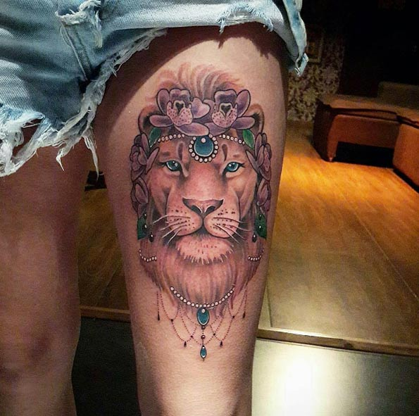 Green and grey shaded lion flower tattoo on left thigh for women