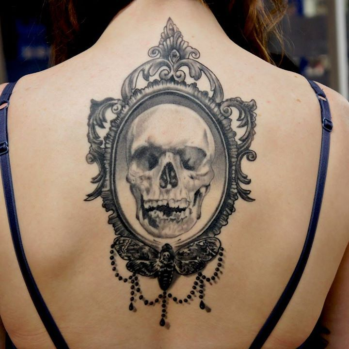 Grey shaded skull on mirror tattoo on mid upper back for women