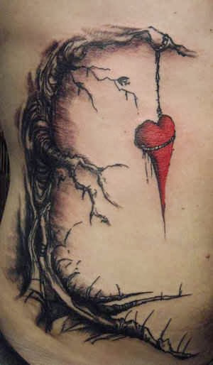 Black and red broken heart hanging from a tree and committing suicide tattoo on body
