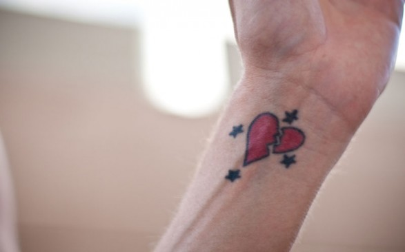 Black and red broken heart with stars tattoo on inner forearm