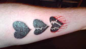 Black broken heart cycle tattoo on arm