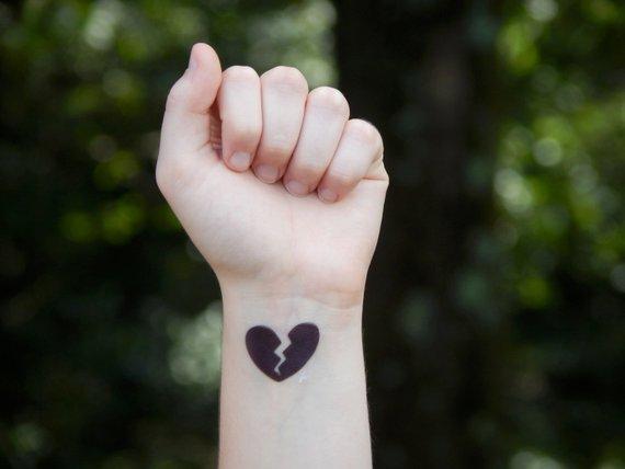 Black broken heart tattoo on inner left hand wrist