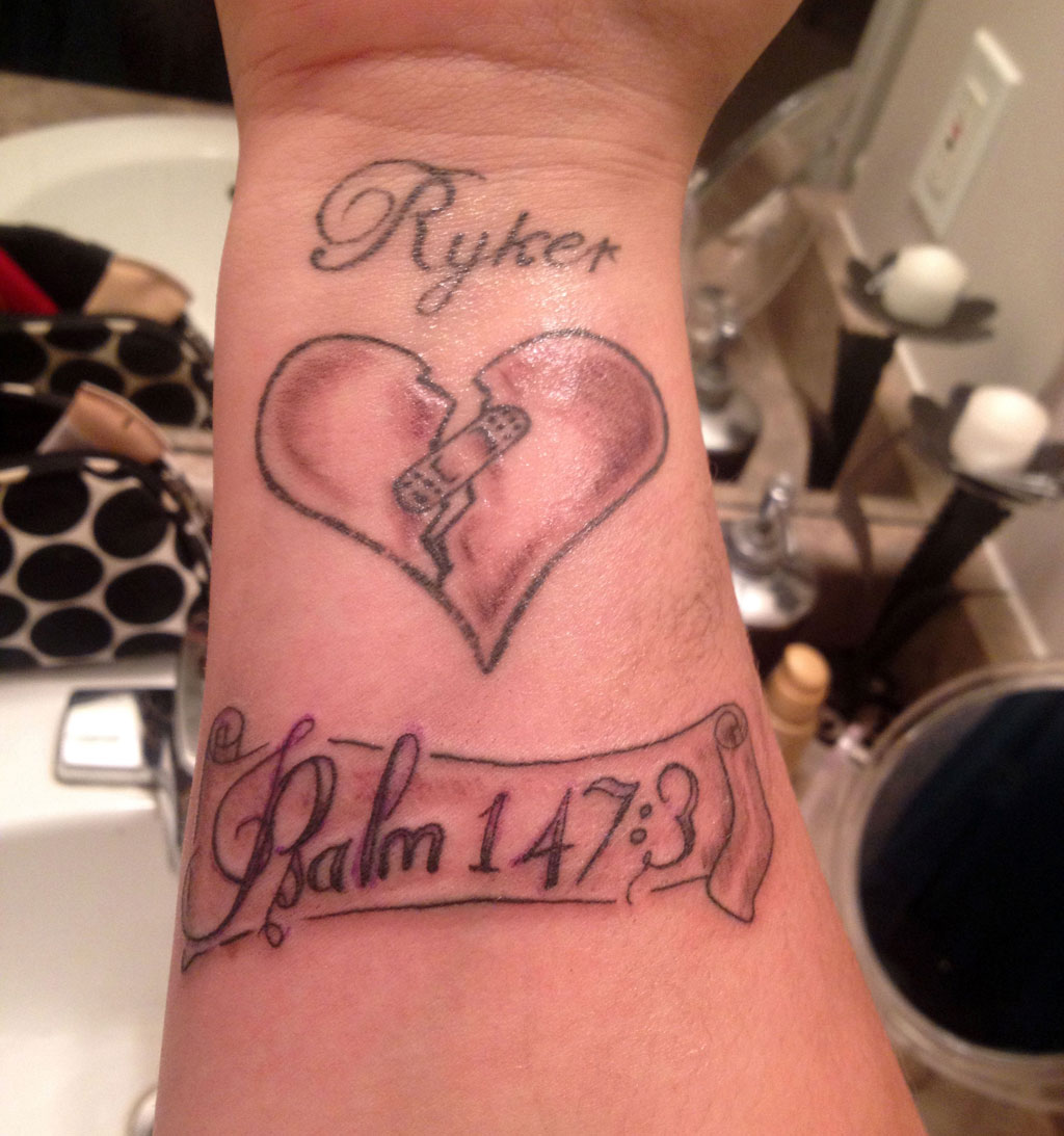 Black shaded bandaged broken heart with name tattoo on inner lower forearm