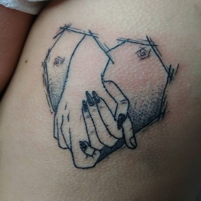 Black sketched holding hands broken heart tattoo on body