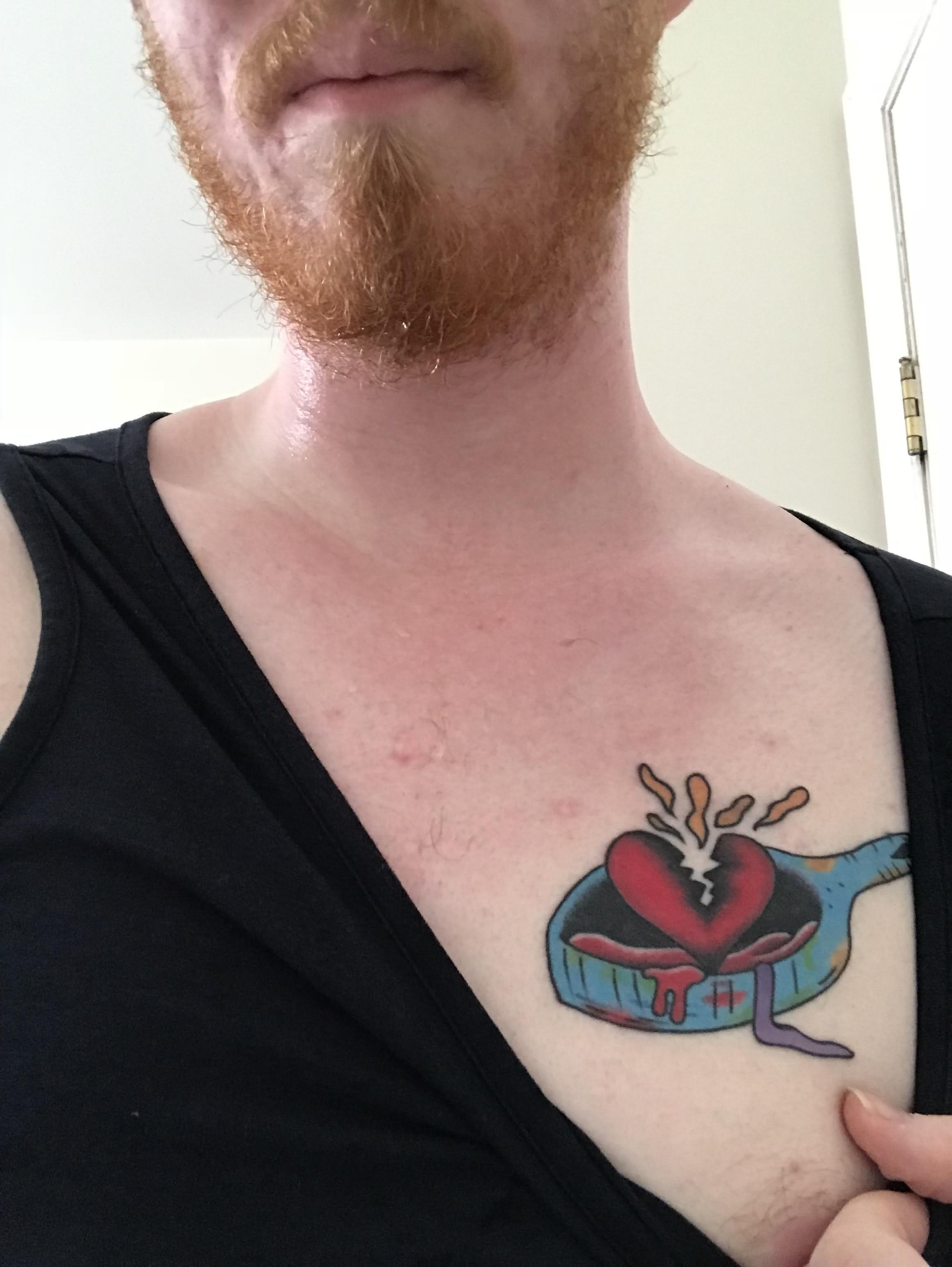 Colored broken heart on pan tattoo on left chest for men