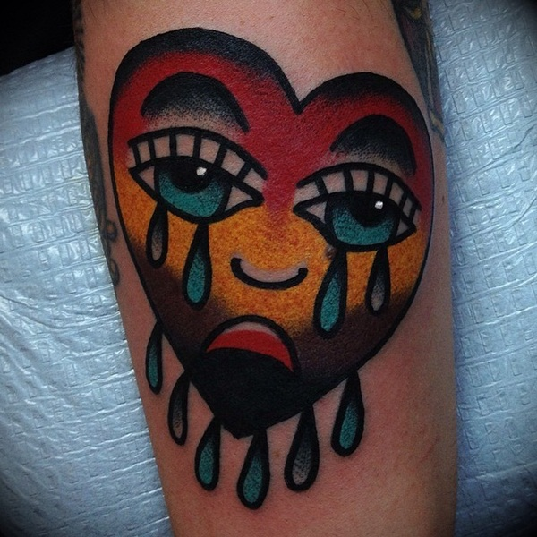 Colored teary eyes broken heart tattoo on arm