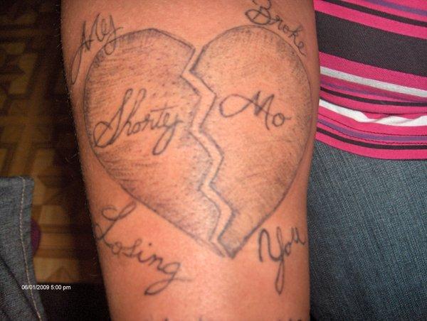 Grey shaded cracking from mid broken heart tattoo on arm by Jakoftrades