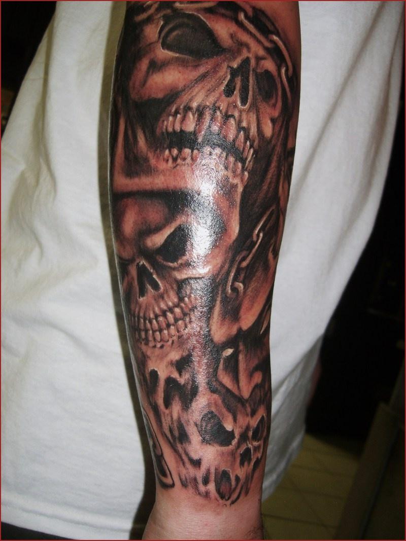Grey Shaded Skulls Tattoo On Lower Sleeve