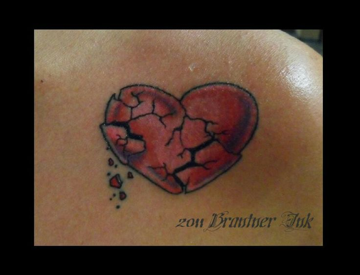 Red and black cracked broken heart tattoo on body
