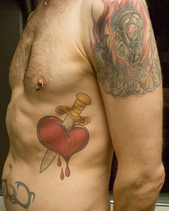 Red and colored broken heart with blood drops and sword tattoo on left mid chest