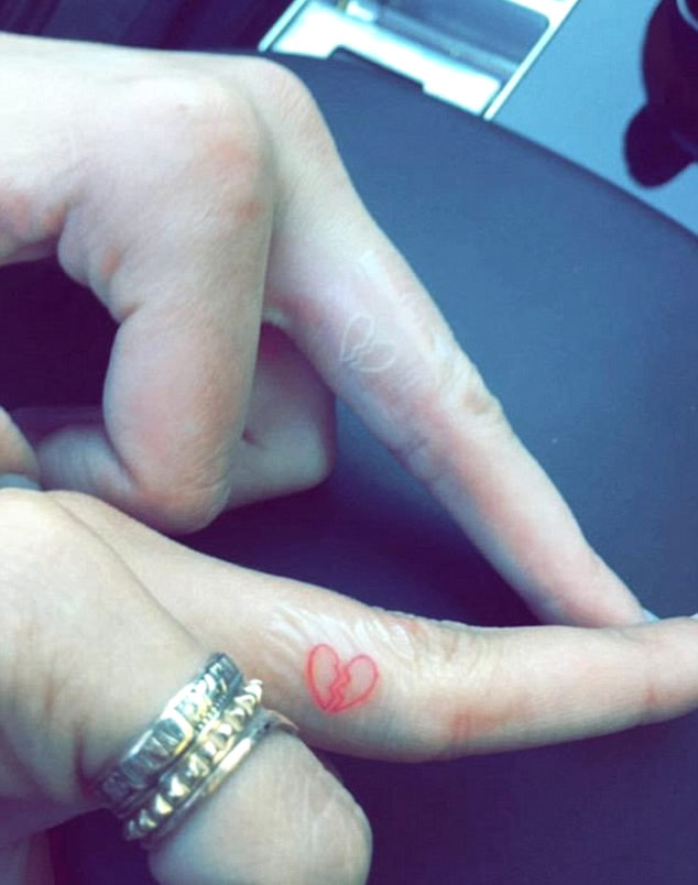 Red and white cracking from mid broken heart tattoo on middle fingers of Kendall Jenner and Hailey Baldwin