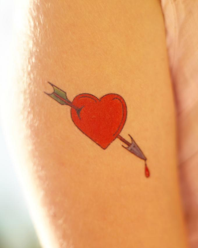 Red broken heart with arrow tattoo on arm