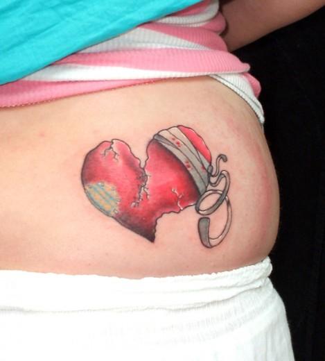 Red cracking broken heart bandaged broken heart tattoo above waist for women
