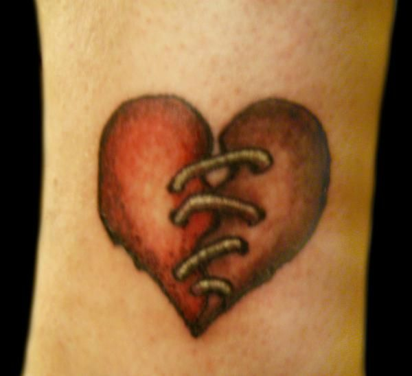 Red sewed broken heart tattoo on body