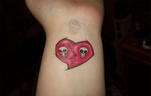 Red, white and black skull with broken heart tattoo on inner forearm